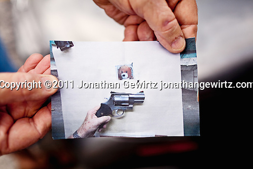 A shooter holds a cell phone photo showing his hand holding a handgun over a test target. The target has holes from two shots that are touching each other.. (Copyright 2011 Jonathan Gewirtz jonathan@gewirtz.net)