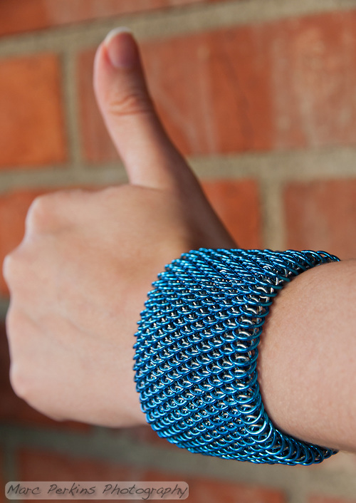 "A blue and silver dragonscale weave maille bracelet on a hand showing the thumbs-up sign.  It's made from saw cut 18 gauge 1/4"" ID blue anodized aluminum rings and saw cut 19 gauge 5/32"" ID bright aluminum rings.  The clasp is a gunmental plated slide clasp.   Handmade by Michelle. (Marc C. Perkins)"