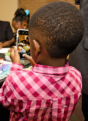 "Ronald Michael Reese takes a photo of his sister, Nia Mya Reese, as she signs copies of her book, ""How to Deal with and Care for Your Annoying Little Brother,"" April 21, 2018, at Homewood Public Library in Birmingham, Ala. Ronald Michael served as the inspiration for the book. Nia Mya, now 9 years old, was 7 when the book was published. (Photo by Carmen K. Sisson/Cloudybright) (Carmen K. Sisson/Cloudybright)"