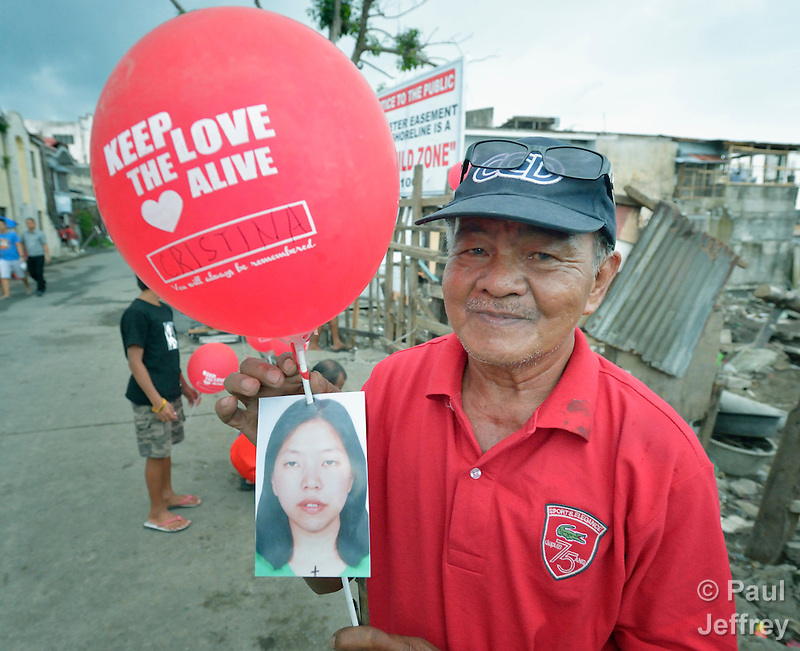 Oscar Mabini holds a balloon celebrating international solidarity with survivors in Tacloban, a city in the Philippines province of Leyte that was hit hard by Typhoon Haiyan in November 2013. The storm was known locally as Yolanda. Mabini also holds a photo of his daughter Cristina, who along with two of her children perished in the storm. (Paul Jeffrey)