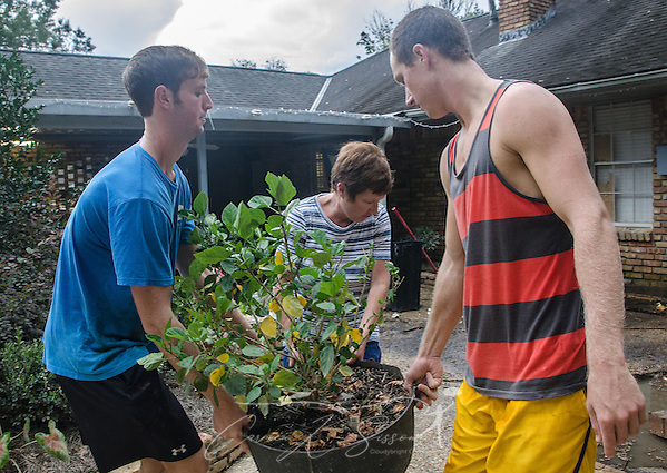 John Whitehead and Jacob Whitehead help their mother, Zanie Whitehead, carry a potted plant, Sept. 4, 2016, in Denham Springs, Louisiana. John Whitehead used his kayak to rescue many of his neighbors after heavy rain caused extended flooding in mid-August. The boys attend Louisiana State University, and the family attends Istrouma Baptist Church in Baton Rouge. (Photo by Carmen K. Sisson) (Carmen K. Sisson/Cloudybright)