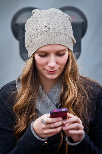 Alyssa Leagjeld consults her iPhone at the downtown block party, Anchorage (Clark James Mishler)