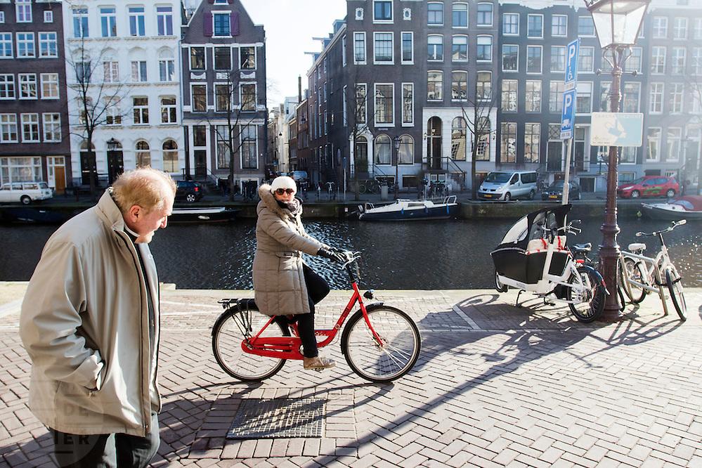 In Amsterdam rijdt een touriste op een huurfiets over de Kloveniersburgwal.