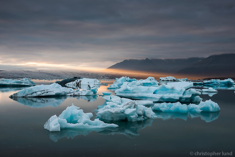 Golden evening rays backlight the blue icebergs on Jökulsárlón glacial lagoon. Jökulsárlón is situated in southeast Iceland, on the borders of Vatnajökull National Park. The lagoon stands 1.5 kilometres (0.93 mi) away from the ocean's edge and covers an area of about 18 km2 (6.9 sq mi). It recently became the deepest lake in Iceland at over 248 metres (814 ft) depth as glacial retreat extended its boundaries. (Christopher Lund/©2012 Christopher Lund)