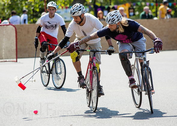 17 AUG 2014 - LONDON, GBR - Players from Camembridge (in white) and Big Fun (in dark blue with pink logo) compete for the ball during the 2014 London Open Bike Polo tournament at Highbury Fields in London, Great Britain (PHOTO COPYRIGHT © 2014 NIGEL FARROW, ALL RIGHTS RESERVED) (NIGEL FARROW/COPYRIGHT © 2014 NIGEL FARROW : www.nigelfarrow.com)