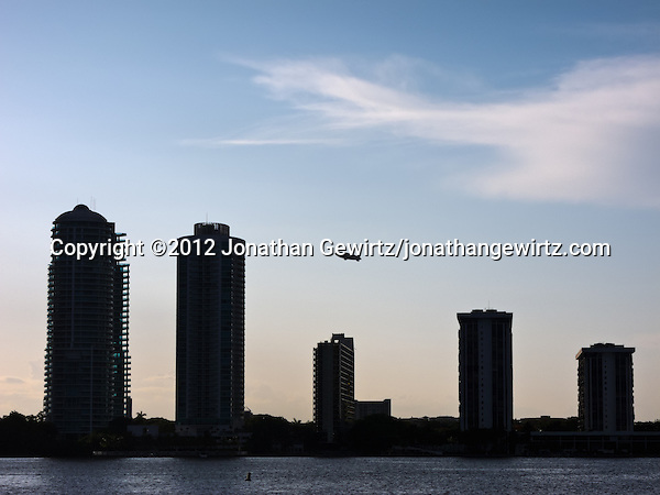 A Goodyear blimp climbs in the late-afternoon sky behind the silhouettes of condominium buildings on Miami's Brickell Avenue. (© 2012 Jonathan Gewirtz / jonathan@gewirtz.net)
