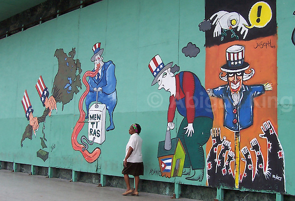 "Woman walks past street art in Cuba. Message reads ""Lies"""