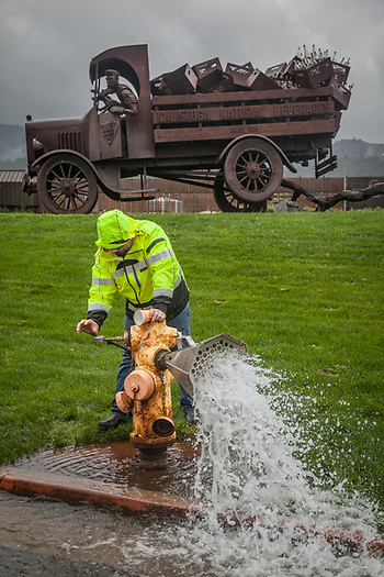 "Calistoga city employee Brandon Gray releases water from a hydrant on Silverado Trail. ""Because of the drought, this is the first time we have been able to do this in the past five years."" (Clark James Mishler)"