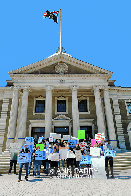 """""""Mineola, NY, USA. April 26, 2021. Activists and civic leaders - including in front row, center, wearing lapis blue face mask and jacket, CLAUDIA BORECKY, a Co-Director of CAWS (Clean Air Water Soil) - rally at Theodore Roosevelt Executive and Legislative Building. Faced with a 26% rate increase from New York American Water going into effect May 1, 2021, activists and residents who are NYAW customers rally. (© 2021 Ann Parry/AnnParry.com)"""