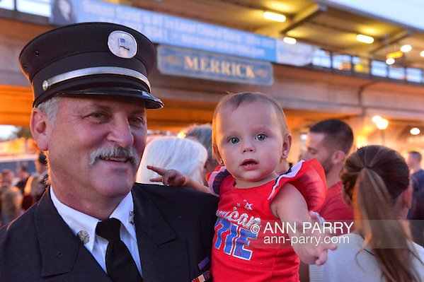 Merrick, New York, USA. September 11, 2015. RILEY E. GIES, one-year-old granddaughter of Fire Chief Ronnie E Gies who died responding to 9/11 NYC Terrorist Attack, is held by CRAIG MALTZ, a Bellmore volunteer firefighter, at Merrick Memorial Ceremony for Merrick volunteer firefighters and residents who died due to 9/11 terrorist attack at NYC Twin Towers. Ex-Chief Ronnie E. Gies of Merrick F.D. and FDNY Squad 288, and Ex-Captain Brian E. Sweeney, of Merrick F.D. and FDNY Rescue 1, died responding to the attacks on September 11, 2001. (Ann Parry/Ann Parry, ann-parry.com)