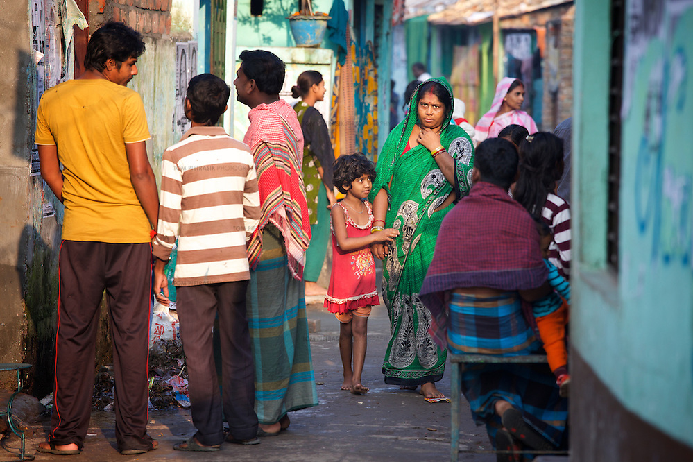 Jhumur Das and her daughter Shobnam Das (age 7) walk through one of the small network of lanes that run through Horijon Polli. Jhumur and her husband are both employed as cleaners. Jhumur lives in Horijon Polli, a slum in which all residents are from the low-caste Hindu sweeper community. The community are ostracised from wider society and there are very few employment opportunities for them beyond cleaning. Oxfam are building a latrine block in Horijon Polli and are working with partners NGO Forum to support residents. Photo: Tom Pietrasik Mymensingh, Bangladesh November 20th 2014 (Tom Pietrasik)