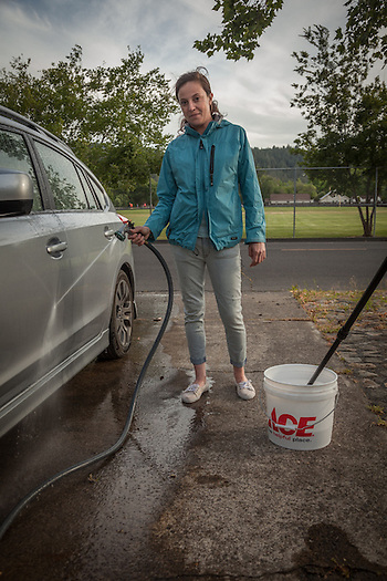 "Bar tender Kaitlin Jones washes her friend's car in front of her home in Calistoga.  ""I love the pace of Calistoga...I grew up in a small town and this feels like home to me."" (Clark James Mishler)"