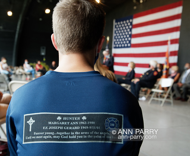East Meadow, New York, U.S. September 10, 2020. JOEY LABO, 16, of Wantagh, seen from back sitting on stage during 9/11 event, wearing a shirt in memory of his uncle Joseph G. Hunter, a FDNY 288 firefighter who died during the attacks, 9/11/01. Nassau County commemorated 19th anniversary of September 11 terrorist attacks with Remembrance Ceremony at Eisenhower Park, with names read of 348 county residents killed that day. (© 2020 Ann Parry/AnnParry.com)