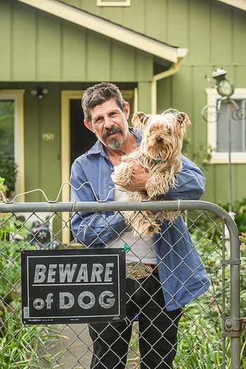 Professional gardener and 40 year resident of Calistoga, Lorenzo Perez stands at his front gate with his guard dog, Gramon. (Clark James Mishler)