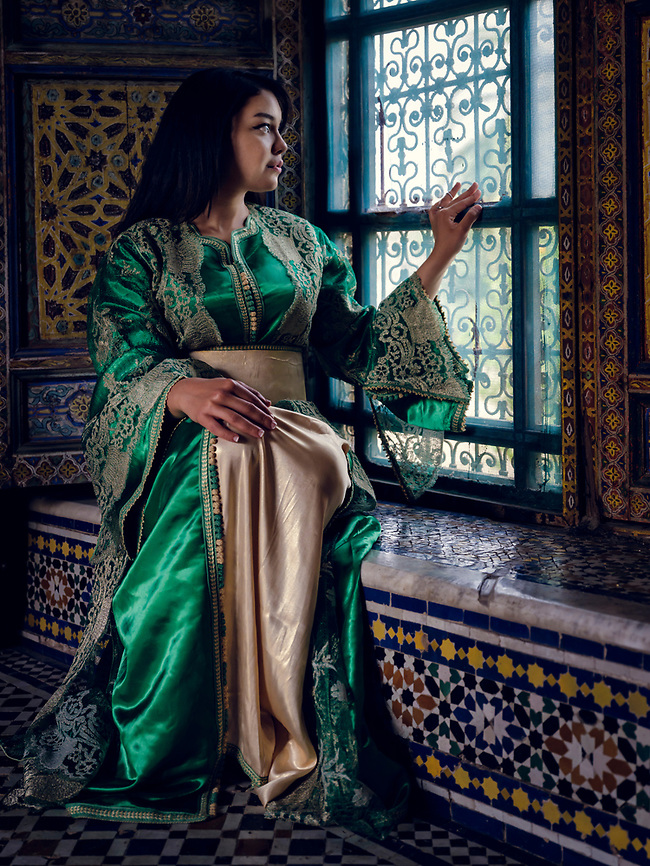 FEZ, MOROCCO - CIRCA APRIL 2017: Young Moroccan woman dressed in traditional clothes posing by a window in the El Glaoui Palace (Daniel Korzeniewski)