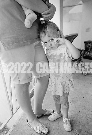 Stevie Nicole Painter, 3, clings to her mother Debbie's leg as her she holds son Brandon, 7 months at the George Washington Motor Lodge, where they are living Tuesday June 23, 1992 in Bensalem, Pennsylvania. (WILLIAM THOMAS CAIN / For The Philadelphia Inquirer) (William Thomas Cain/Cain Images)