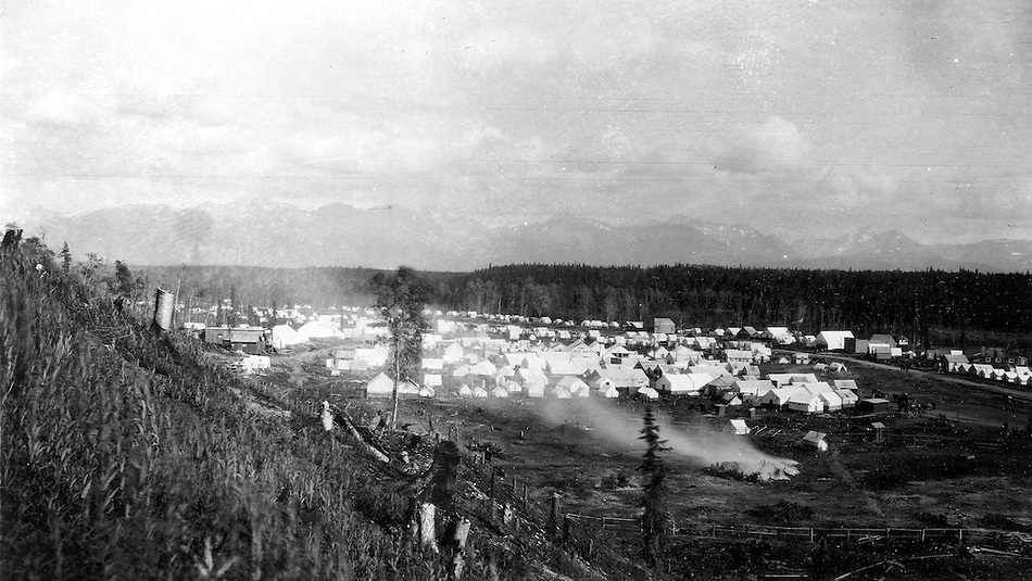 View of the temporary railroad construction town consisting of tents and a few buildings along Ship Creek in Anchorage, Alaska, 1915.  Identifiable businesses in the image include: The Crest House, Sourdough Lodging, and Montana Pool Room. Note the recently cut tree stumps on the slope in the foreground and the smoke from the burning pile of brush in the lower right. This image was probably taken within a few days of Capps arrival in Anchorage on June 14, 1915.  Photo by S.R. Capps, 1915, U.S Geological Survey Photo Library. (S.R. Capps, U.S. Geological Survey Photo Library)