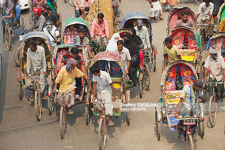 "DHAKA, BANGLADESH - FEBRUARY 22, 2014: Rickshaws transport passengers in Dhaka, Bangladesh. About 500 000 rickshaws daily cycle in Dhaka, nicknamed ""the rickshaws capital of the world"". (Dmitry Chulov)"