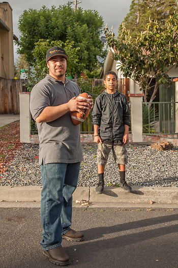 Neighbor Francisco Otero plays catch with his brother, Javier (13), in front of their house on Myrtle Street in Calistoga. (Clark James Mishler)