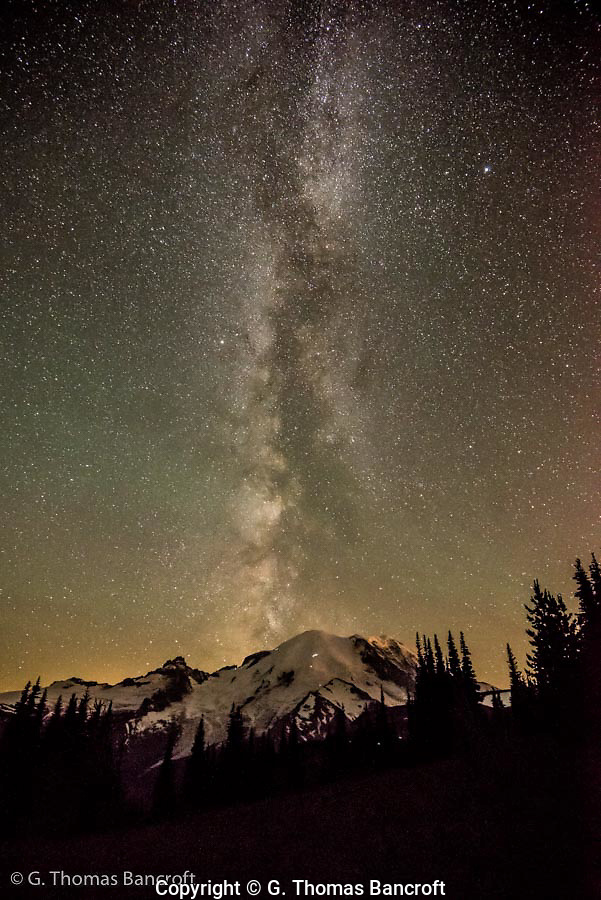 By 2AM the Milky Way is right over the summit of Mt Rainier and looks as though it is coming out of the volcano. Three parties climb the north side of the volcano and at least three more are climbing the ridge along the east side. (G. Thomas Bancroft)