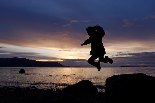 Girl jumping from rock on beach at sunset, Lummi Island, Washington (Copyright Brad Mitchell Photography.9601 Wall St.Snohomish, WA 98296.USA.425-418-7279.brad@bradmitchellphoto.com)