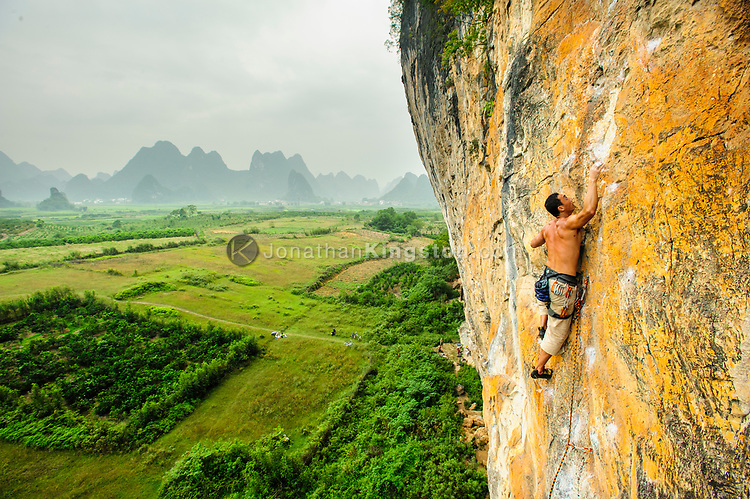 A male rock climber scales an orange cliff at an area known as The White Mountain near Yangshuo, China (Model Released, Sean Ouyang). (Jonathan Kingston)