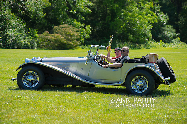 Westbury, New York, USA. June 12, 2016. MARK OFFENBERG, of Valley Stream, drives his silver 1973 Intermeccanica Squire SS-100 Italian luxury classic roadster while his passenger holds 3rd Place Trophy the car won in the foreign car category at the Antique and Collectible Auto Show at the 50th Annual Spring Meet at Old Westbury Gardens, in the Gold Coast of Long Island, and sponsored by Greater New York Region, GNYR, Antique Automobile Club of America, AACA. Car is the 46th of only 50 Intermeccanica's coachbuilt in Turin, Italy. Participating vehicles in the judged show included hundreds of domestic and foreign, antique, classic, collectible, and modern cars and trucks. (Ann Parry/Ann Parry, ann-parry.com)