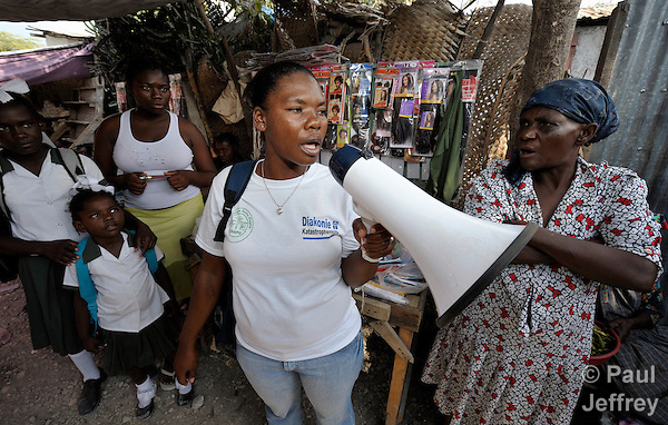 Isma Alexis (with megaphone), a community health worker for Oganizasyon Sante Popilè (OSAPO), speaks in the town market to residents of Montrouis, Haiti, about steps they can take to prevent the spread of cholera, which appeared on the quake-ravaged Caribbean island nation in late 2010. OSAPO's work is supported by Diakonie Katastrophenhilfe and the Lutheran World Federation, both members of the ACT Alliance. Health workers from OSAPO go out to surrounding neighborhoods and communities in teams of three, providing education, distributing anti-bacterial soap and oral rehydration salts, and referring ill patients to the OSAPO clinic....