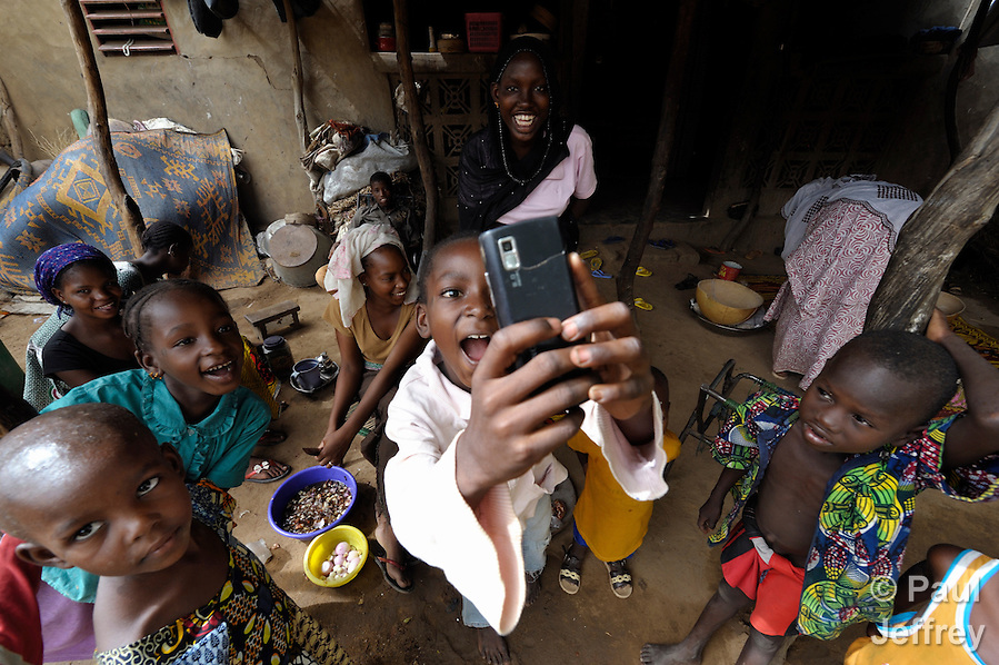 Internally displaced girls living in Segou, Mali, take a photograph of a photographer with their mobile phone. (Paul Jeffrey)