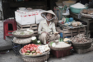 Vegetable Seller in Hoi An Market, Vietnam. The crowded streets and stalls are full to bursting point with locals buying and selling fruit, vegetables, fresh fish and hand-made crafts. It is a great place to spend an afternoon exploring, trying traditional Vietnamese foods, chatting the market stall owners and learning the art of bartering. No matter how hard you try you will NEVER get anything for the same price as the locals!