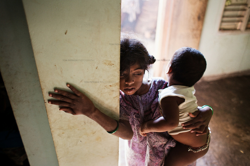 While her step-mother makes breakfast, Vijyashree Viswanathan cares for her brother at home in Thalanguda. Vijyashree lost her mother and first brother to the Tsunami. Since then her father has remarried and now has two children by his second wife. Vijitha and Vijyashree Viswanathan, now age 12 and 10, lost their mother and younger brother to the 2004 Asian Tsunami. The sisters continue to live with their father Viswanathan in a small house in the fishing village of Thalanguda, 5km from Cuddalore. The house does not have a toilet and water is supplied for only a short period of the day. Viswanathan married Kayalvizhi just over a year after the tsunami and the couple now have a son born in December 2006. Of the two sisters it was the elder Vijitha who initially appeared more distressed at her mother's death. But in the subsequent three years she has come to terms with her loss and seems better equipped to face the challenges of growing up without the support of her mother. In contrast Vijyashree, whos younger age may have insulated her from some of the grief experience by her sister, has fallen back in her studies becoming moody, withdrawn and reticent. Vijyashree has suffered fits for a number of years but in the past twelve months these have become more frequent. Viswanathan blames the drugs prescribed to treat his daughter's condition for her moodiness. Another explanation could be the arrival of Vijyashree's half-brother Sanjay with whom she must now compete for the affections of her father. Kayalvizhi does not appear particularly sensitive to the needs of her adopted daughters though her position cannot be easy, particularly when burdened with the task of raising a baby. Viswanathan's sister-in-law Shanthi is especially scathing of Kayalvizhi's indifference to Vijitha and Vijyashree and questions whether the girls should be expected to clean the house, clean utensils and prepare themselves for school. Shanthi complains that the girls must come to her for affect (Tom Pietrasik)