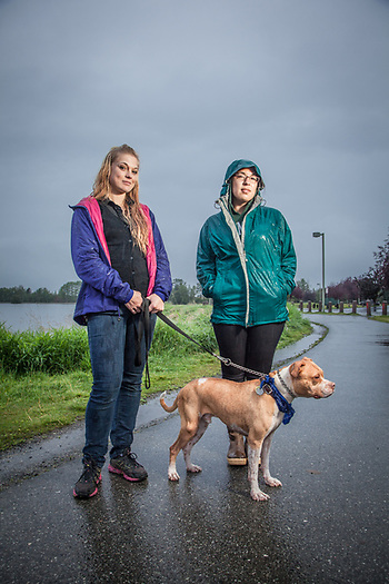 Alunna Purday and Agatha Erickson with their dog, Cooper, on a rainy evening near Westchester Lagoon, Anchorage (Clark James Mishler)