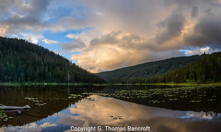 The clouds were shifting rapidly across Lake Janus as the sun was preparing to set.  The lake was flat, forming a wonderful mirror for the changing sky.  I found a good rock to sit and watch.  It was an uplifting period and a great end to a wilderness day. (G. Thomas Bancroft)