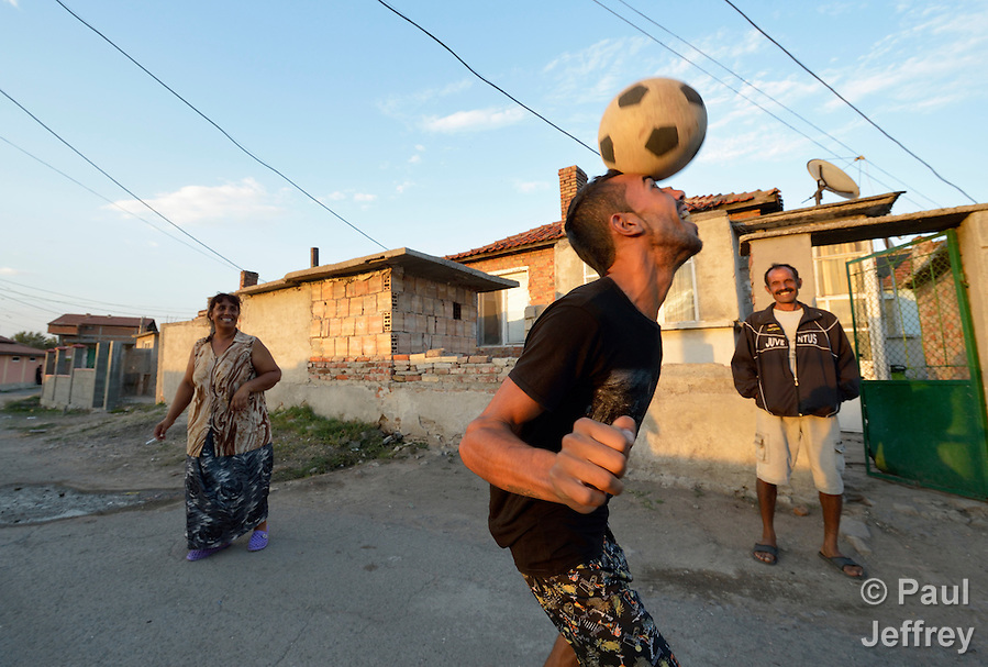 A man heads a soccer ball while playing football in the street in the largely Roma neighborhood of Gorno Ezerovo, part of the Bulgarian city of Burgas. Residents here don't self-identify much as Roma, because of the negative connotations associated with the word, so many refer to themselves as a Turkish-speaking minority. (Paul Jeffrey)