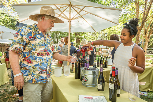 Summers Estate Wines representative Bryanna McKinney serves up a sample to Joe Seiberlich at the Calistoga Wine Experience at Pioneer Park. (Clark James Mishler)