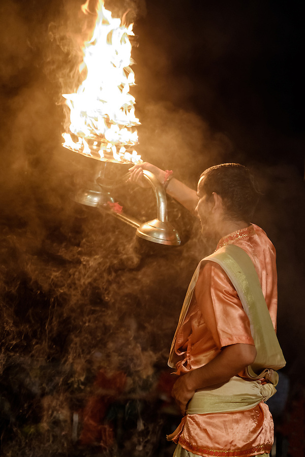 VARANASI, INDIA - CIRCA NOVEMBER 2016: Young pandit performing the Ganga Aarti ceremony at the Dasaswamedh Ghat in Varanasi. The Aarti is a powerful and uplifting spiritual ritual that takes place every evening at dusk. Varanasi is the spiritual capital of India, the holiest of the seven sacred cities and with that many rituals and offerings are performed daily by priests and hindus. (Daniel Korzeniewski)