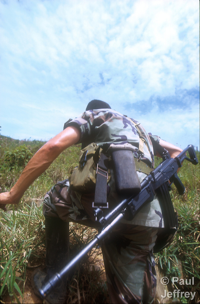 A Colombian soldier climbs through the hills above Cubara in 2010 as part of a force protecting exploratory drilling sites of Occidental Petroleum. The U.S.-based company was drilling on land which U'wa indigenous leaders claimed had bee stolen from their tribal reservation. (Paul Jeffrey)