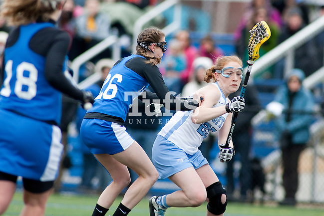 03/10/2012- Medford, Mass. - Tufts attack Gabby Horner, A14, gets checked in Tufts 8-7 season opening win over Hamilton on Mar. 10, 2012. (Kelvin Ma/Tufts University)