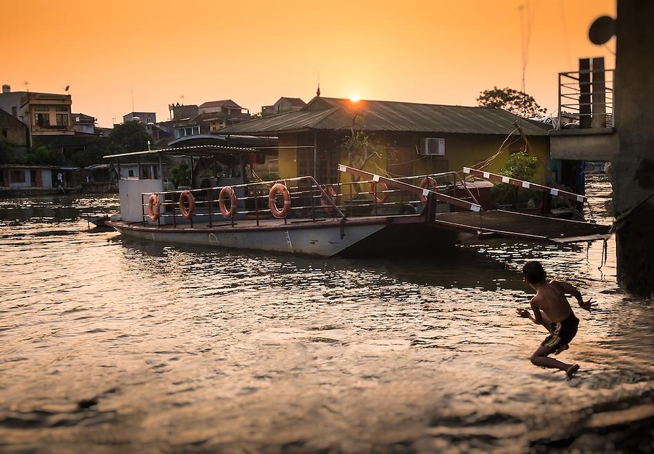 VAN HA, VIETNAM - CIRCA SEPTEMBER 2014: Boy jumping in the Cau river in the afternoon at the Lang Gom Tho Ha village. The village belongs to the Van Ha commune, it is located 50km away from Hanoi in Northern Vietman (Daniel Korzeniewski)