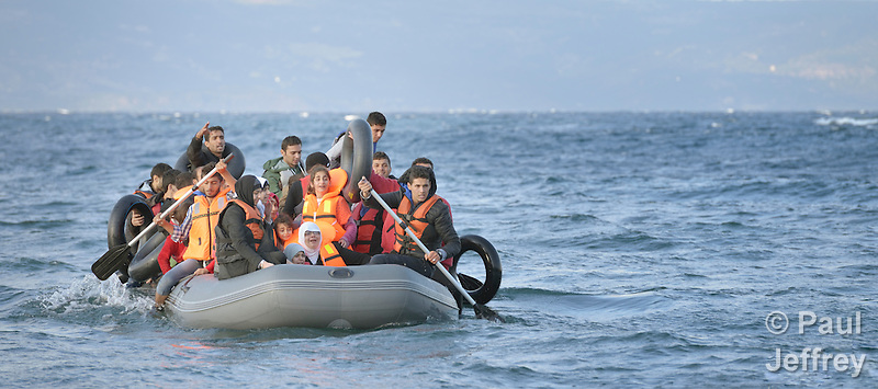 Refugees travel in a rubber boat across the Aegean Sea from Turkey to the Greek island of Lesbos on October 30, 2015. They were received on a beach near Molyvos by local and international volunteers, then proceeded on their way toward western Europe. The boat was provided by Turkish traffickers to whom the refugees paid huge sums to arrive in Greece. Yet the motor quit during the crossing and the refugees were forced to paddle for several hours. (Paul Jeffrey)