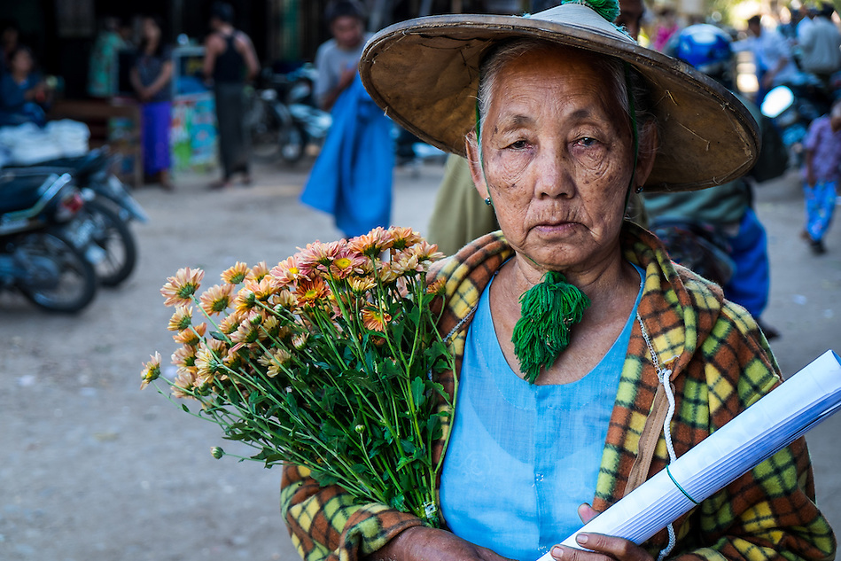 BAGAN, MYANMAR - CIRCA DECEMBER 2013: Old Burmese woman walking in the streets of  Nyaung U market close to Bagan in Myanmar with some flowers. (Daniel Korzeniewski)