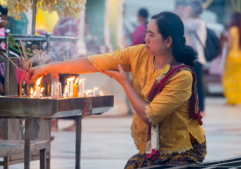 YANGON, MYANMAR - CIRCA DECEMBER 2013: Woman lighting incense in the Shwedagon Pagoda, a famous landmark in Yangon (Daniel Korzeniewski)