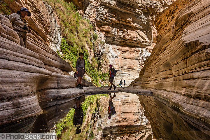 Hikers reflect in a plunge pool in Fern Glen slot canyon at Colorado River Mile 168.6. Day 12 of 16 days rafting 226 miles down the Colorado River in Grand Canyon National Park, Arizona, USA. (© Tom Dempsey / PhotoSeek.com)