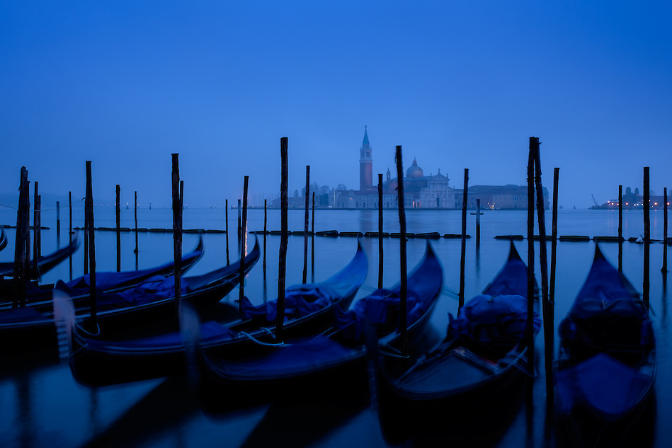 VENICE, ITALY - CIRCA MAY 2015: View of typical Venetian gondolas with the Grand Canal and San Giorgio Maggiore at dawn. (Daniel Korzeniewski)