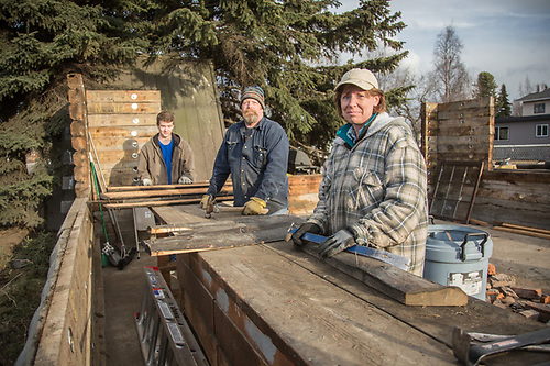 """We've been working on this house since Christmas…it's our plan to reconstruct it in Homer.""  Scott Gorder and his girlfriend, Barbara Keller, and his son, Colten, disassemble a historic log structure at the corners of 15th and H Streets. (© Clark James Mishler)"