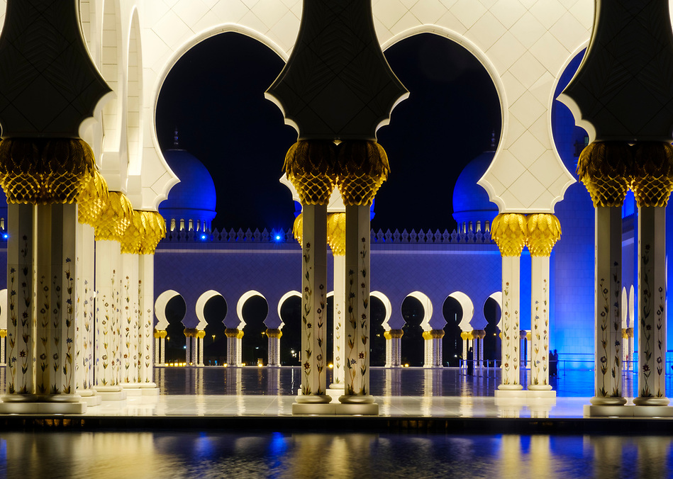 UNITED ARAB EMIRATES, ABU DHABI - CIRCA JANUARY 2017: Pool, arches and columns of the Sheikh Zayed Mosque at night. (Daniel Korzeniewski)