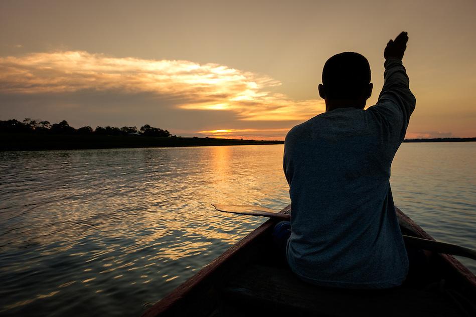 LORETO, PERU - CIRCA OCTOBER 2015: Local guide marking directions during sunset in the Ucayali river in the Peruvian Amazon. (Daniel Korzeniewski)