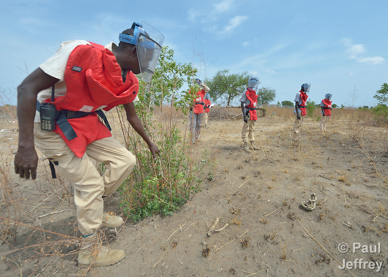 John Simba, a member of an ACT Alliance team, searches for unexploded ordnance in a civilian area near the South Sudan town of Bor, which has been the scene of heavy fighting between government troops and rebels since a dispute within the ruling party turned violent in December 2013 and quickly ripped the newly independent nation along ethnic and tribal lines. The explosive ordnance disposal team is part of the humanitarian mine action program of Dan Church Aid, a member of the ACT Alliance. The program also deploys mine risk education teams to help villagers identify and understand the dangers of unexploded ordnance and land mines from this most recent conflict as well as ordnance left over from decades of civil war. (Paul Jeffrey)
