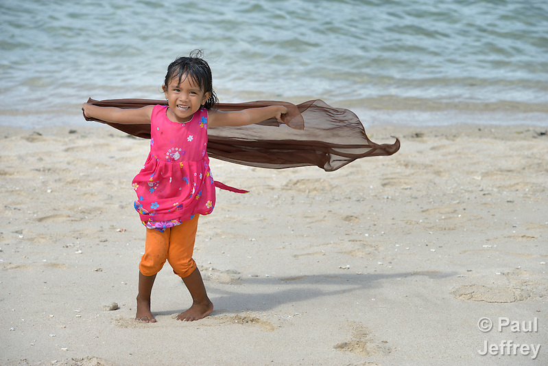 Five-year old Vera Vernanda plays on the beach at Lhok Me, in Indonesia's Aceh province. The girl's mother sells coconuts and soft drinks to tourists on the beach. The family was left homeless by the 2004 tsunami, but YEU, a member of the ACT Alliance, worked with the village to build new houses in a safer area, as well as help revitalize their income generating activities, including Vera's mother's small business. The tsunami killed 221,000 people in Aceh province and left more than 500,000 displaced. Parental consent obtained. (Paul Jeffrey)