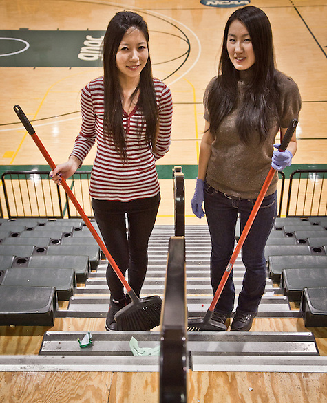 UAA foreign students from Mongolia, Toma Damba and Sanna Ganchuluun, help clean up after a UAA Basketball game. (Clark James Mishler)